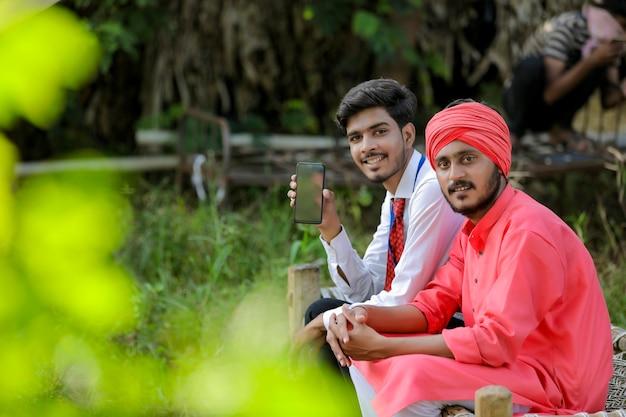 Jonge indiase bankambtenaar met mobiel scherm met boer