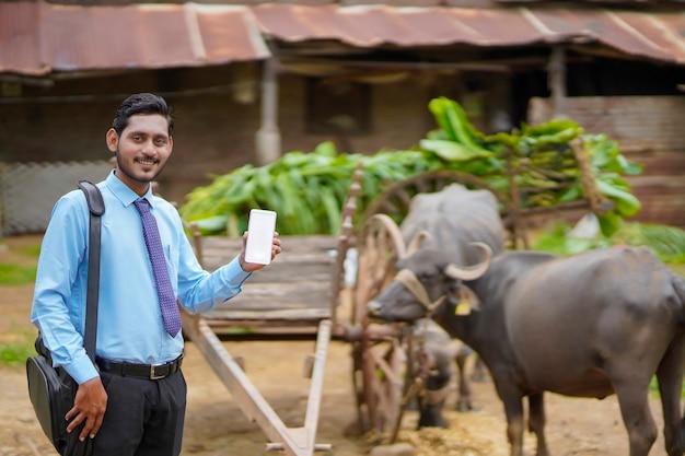 Jonge indiase bankfunctionaris of agronoom die smartphone laat zien in het boerenhuis