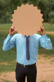 Jonge indiase bankier of officier die een leeg bord op de achtergrond van de natuur toont.