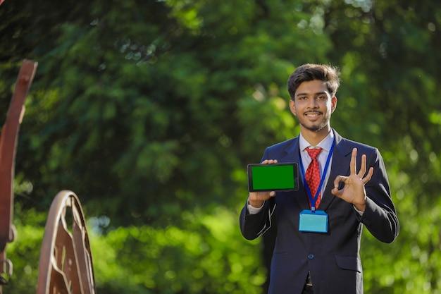 Jonge indiase bankier smartphone tonen op veld