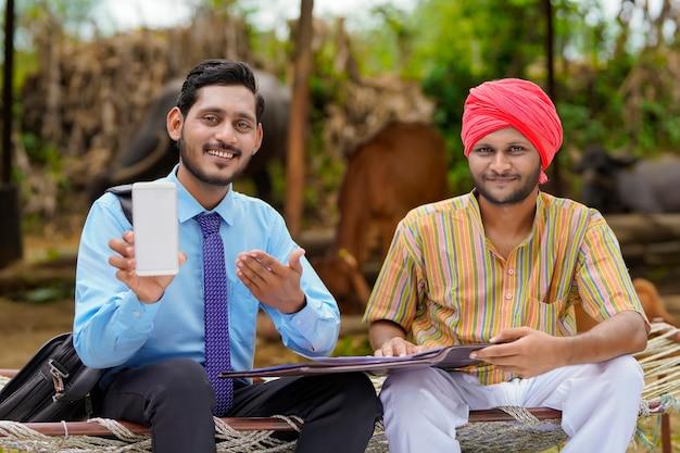 Jonge indiase bankmedewerker of agronoom die smartphone met boer op zijn boerderij laat zien