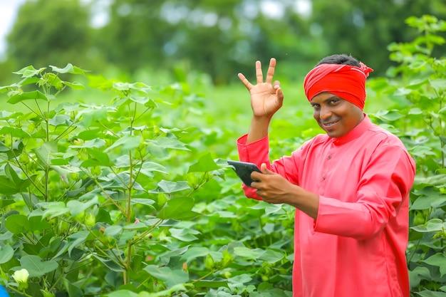 Jonge indiase boer die mobiel gebruikt voor videogesprek