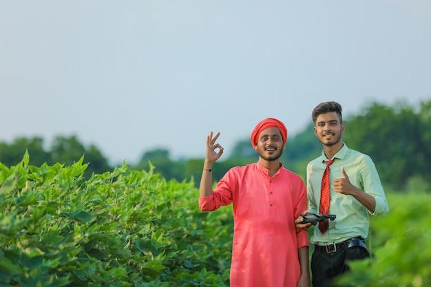 Jonge indiase boer en agronoom die dreunen op landbouwgebied