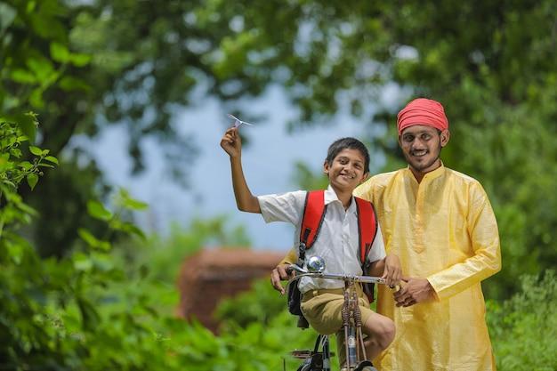 Jonge indiase boer en zijn zoon die naar school gaan