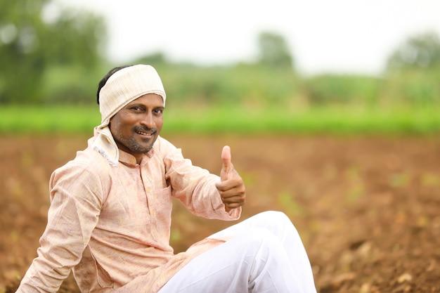 Jonge indiase boer in traditionele kleding en bonzen op het veld.