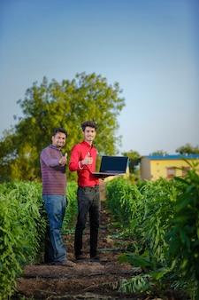 Jonge indiase boer met agronoom op veld