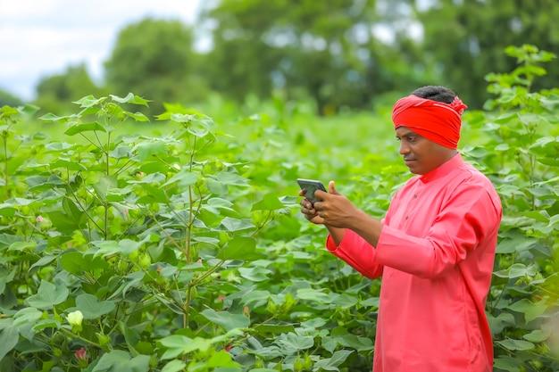 Jonge indiase boer met behulp van mobiele telefoon op landbouwgebied