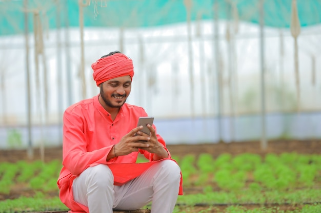 Jonge indiase boer met behulp van slimme telefoon op kas