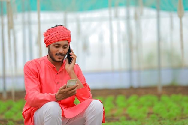 Jonge indiase boer met behulp van smartphone op kas