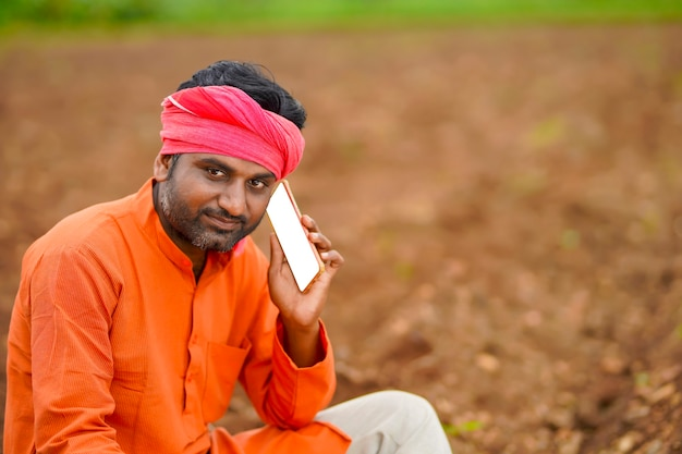 Jonge indiase boer of arbeider praten op mobiele telefoon op katoenveld