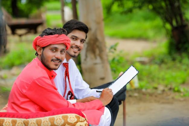 Jonge indiase boer ondertekenen op document met bankier thuis