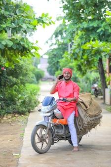 Jonge indiase boer praten op mobiele telefoon