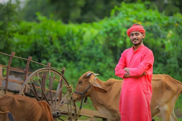 Jonge indiase boer staande met vee boerderijdier