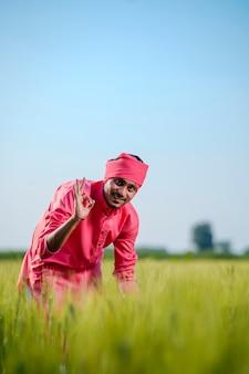 Jonge indiase boer staande op groen tarweveld op hemelachtergrond
