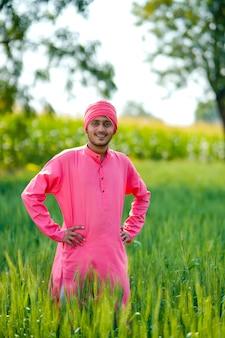 Jonge indiase boer staande zijn tarweveld en gelukkige uitdrukking geven