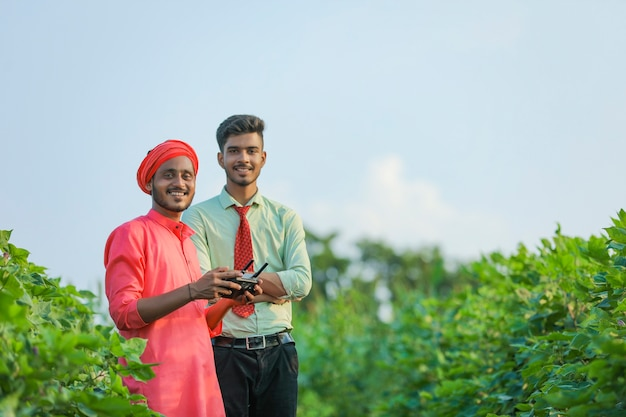 Jonge indiase boer ver in de hand houden en vliegende drone met agronoom op landbouwgebied controleren