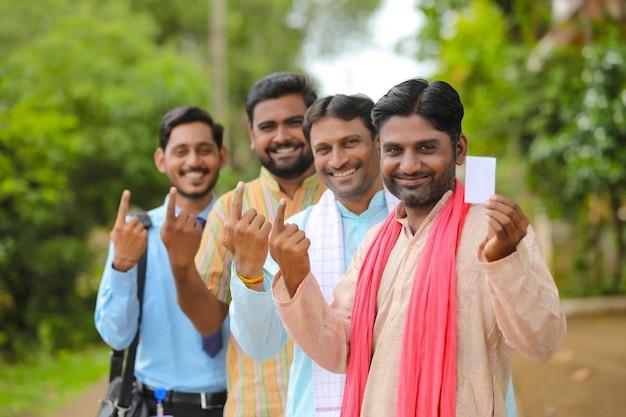 Jonge indiase boeren die vinger tonen na het stemmen met officieren.