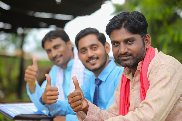 Jonge indiase boeren slaan de handen ineen met bankier of agronoom.