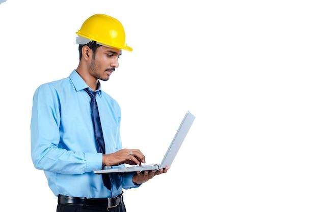 Jonge indiase ingenieur in uniform en met behulp van laptop op witte achtergrond.
