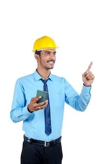 Jonge indiase ingenieur of bouwplaatsmedewerker die smartphone gebruikt.