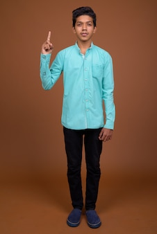 Jonge indiase jongen draagt blauw shirt op zoek slim tegen bruine achtergrond