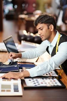 Jonge indiase kleermaker controleert catalogus met trendy kleuren en stofstalen voor nieuw maatpak
