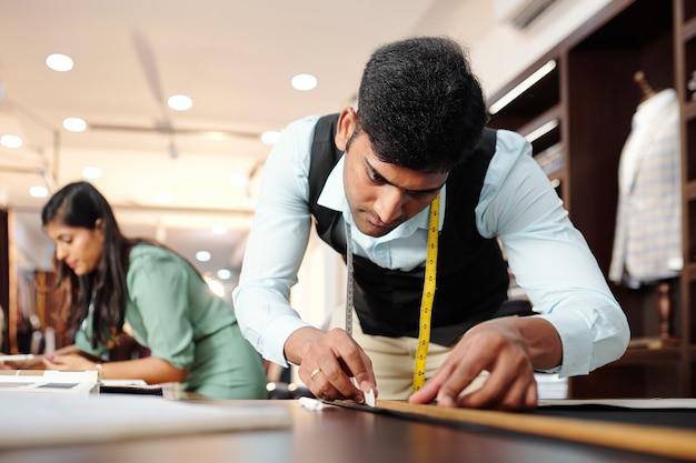 Jonge indiase kleermaker die details van jasje uitsnijdt wanneer zijn collega met catalogus op achtergrond werkt