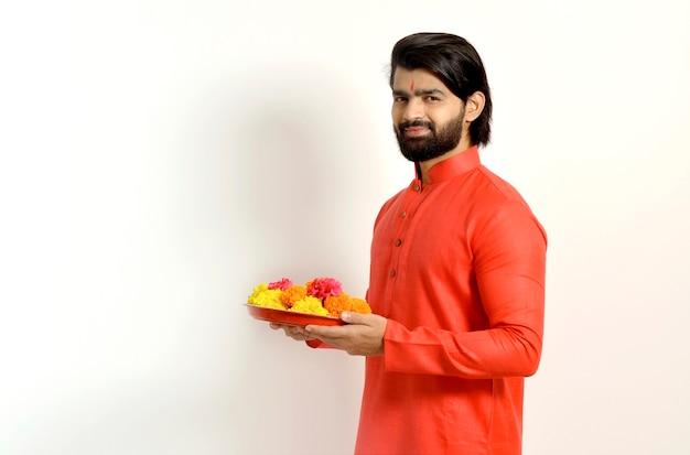 Jonge indiase knappe man met kurta, zijaanzicht, bloem thali vast te houden
