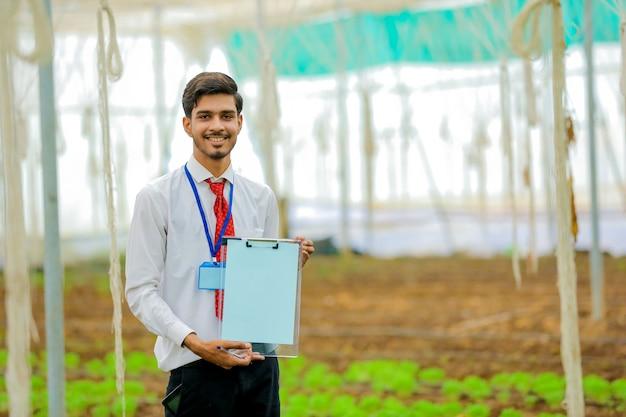 Jonge indiase landbouwingenieur die notitieblok toont en wat informatie verzamelt in de kas