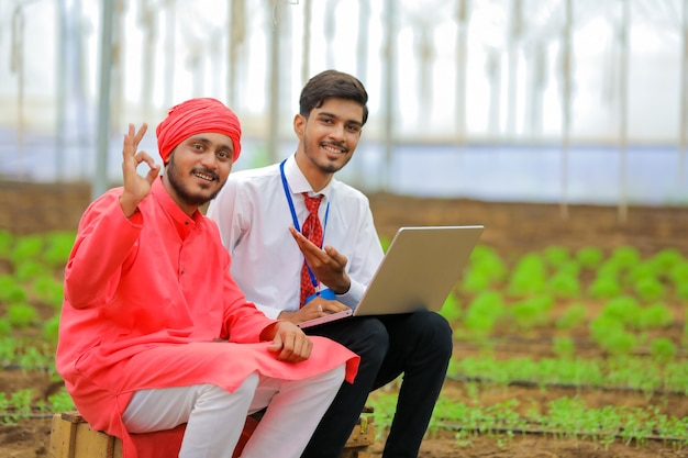 Jonge indiase landbouwingenieur en boer bij kas