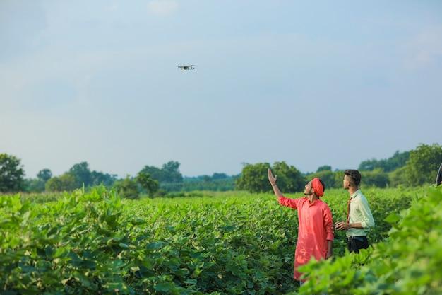 Jonge indiase landbouwingenieur en boer met behulp van drone voor controle op landbouwgebied