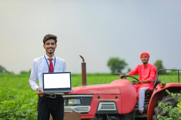 Jonge indiase landbouwingenieur laptop scherm tonen