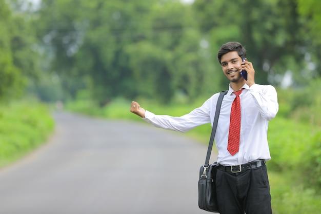 Jonge indiase landbouwingenieur met behulp van slimme telefoon aan de kant van de weg en lift te vragen
