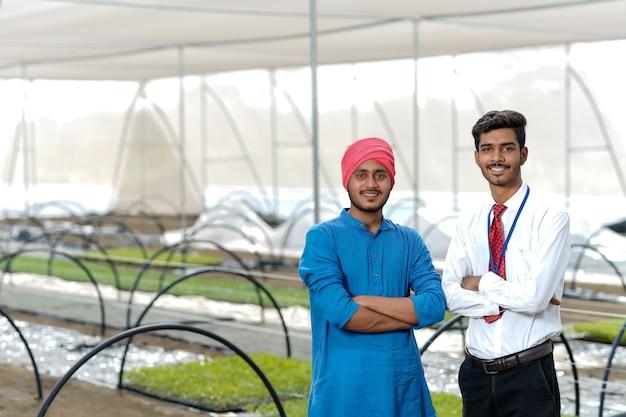 Jonge indiase landbouwingenieur met boer op kas