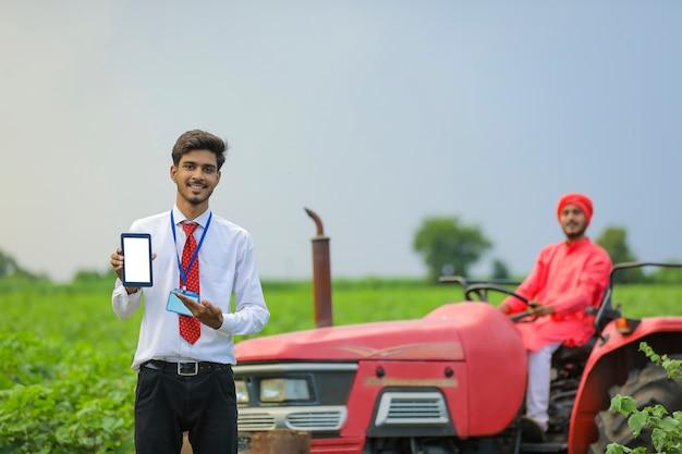 Jonge indiase landbouwingenieur met smartphone of tablet op veld
