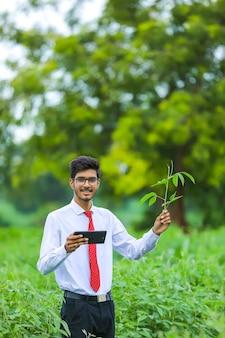 Jonge indiase landbouwingenieur met smartphone op veld