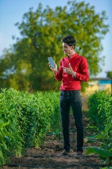 Jonge indiase landbouwingenieur met smartphone