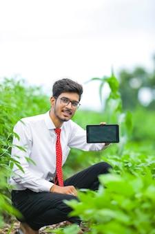 Jonge indiase landbouwingenieur smartphone tonen op veld