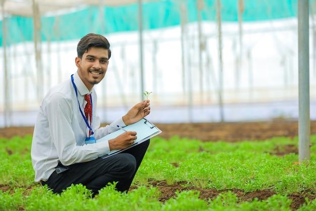 Jonge indiase landbouwingenieur verzamelt wat informatie in de kas
