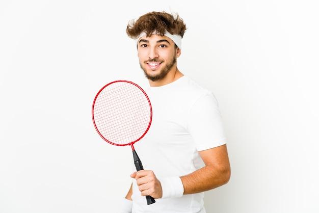 Jonge indiase man badminton spelen kijkt opzij glimlachend, vrolijk en aangenaam.