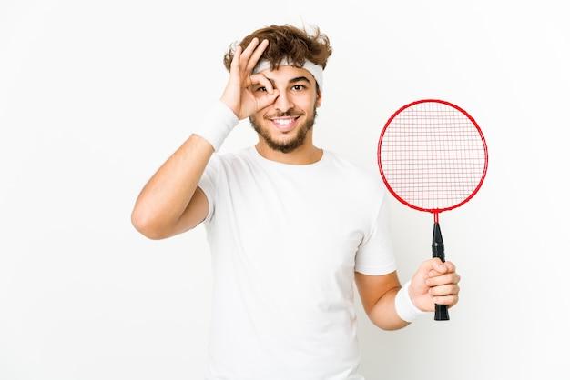 Jonge indiase man badminton spelen opgewonden houden ok gebaar op oog.