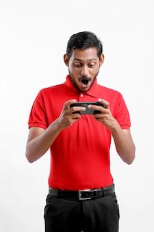 Jonge indiase man die schokkende uitdrukking geeft na het zien in smartphone