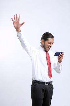 Jonge indiase man die schokkende uitdrukking geeft na het zien van een smartphone.