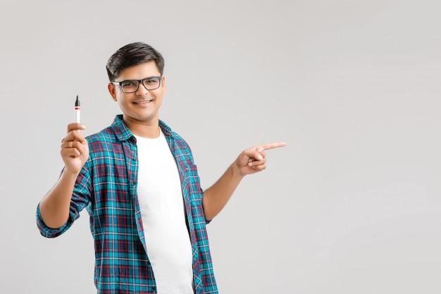 Jonge indiase man draagt een bril en schrijft iets op een glazen schrijfbord