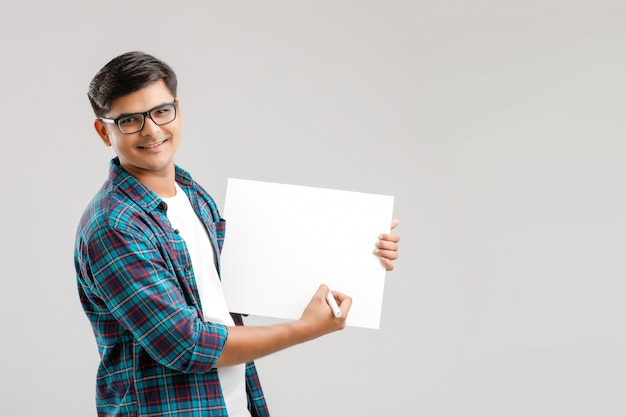 Jonge indiase man draagt een bril en schrijft iets op een leeg schrijfbord