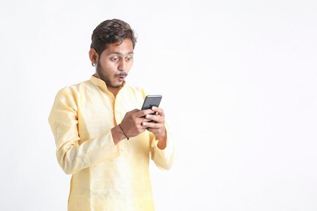 Jonge indiase man in traditie slijtage en met behulp van smartphone op witte muur