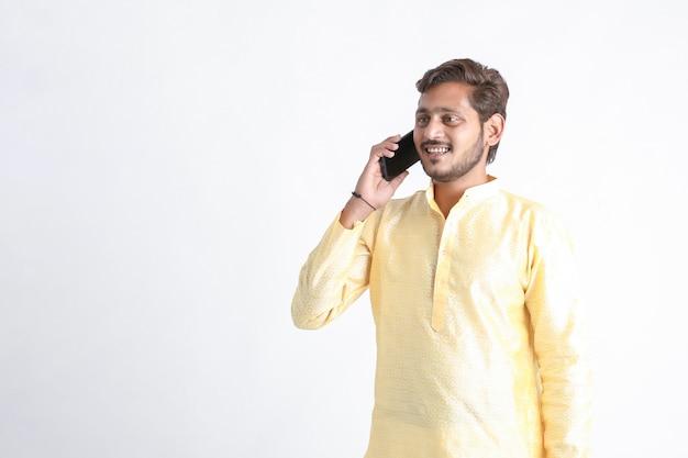 Jonge indiase man in traditionele slijtage en praten over smartphone