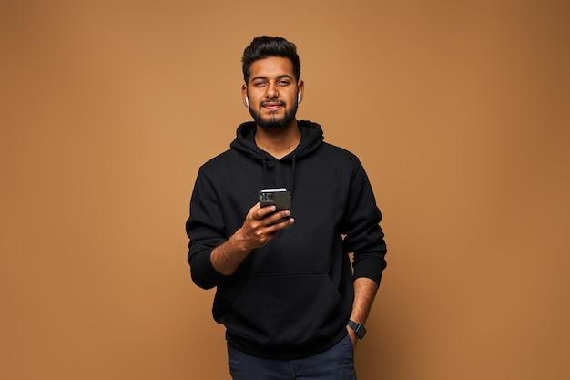 Jonge indiase man in zwarte hoody die met zijn mobiele telefoon op de muur surft