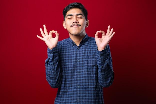 Jonge indiase man met een casual shirt dat over een geïsoleerde rode achtergrond staat, ontspant en lacht met gesloten ogen terwijl hij een meditatiegebaar met vingers doet. yoga-concept.