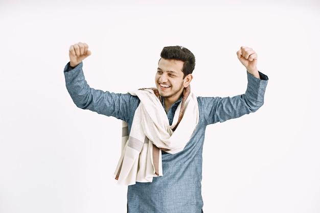 Jonge indiase man met handen omhoog. dansen op een witte muur, geïsoleerd.